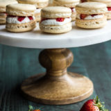 Strawberry Shortcake Macarons presented on a big tray with a few fresh strawberries under it