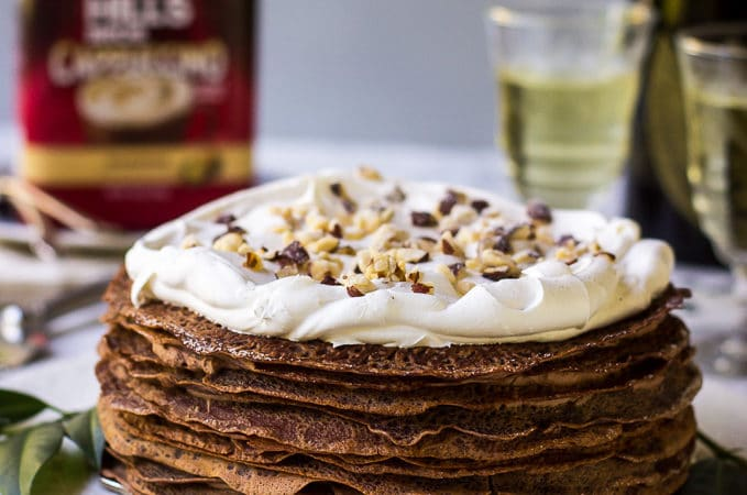 Double-Chocolate-Hazelnut-Crepe-Cake on white platter with champagne glasses, bottle and coffee can in background.
