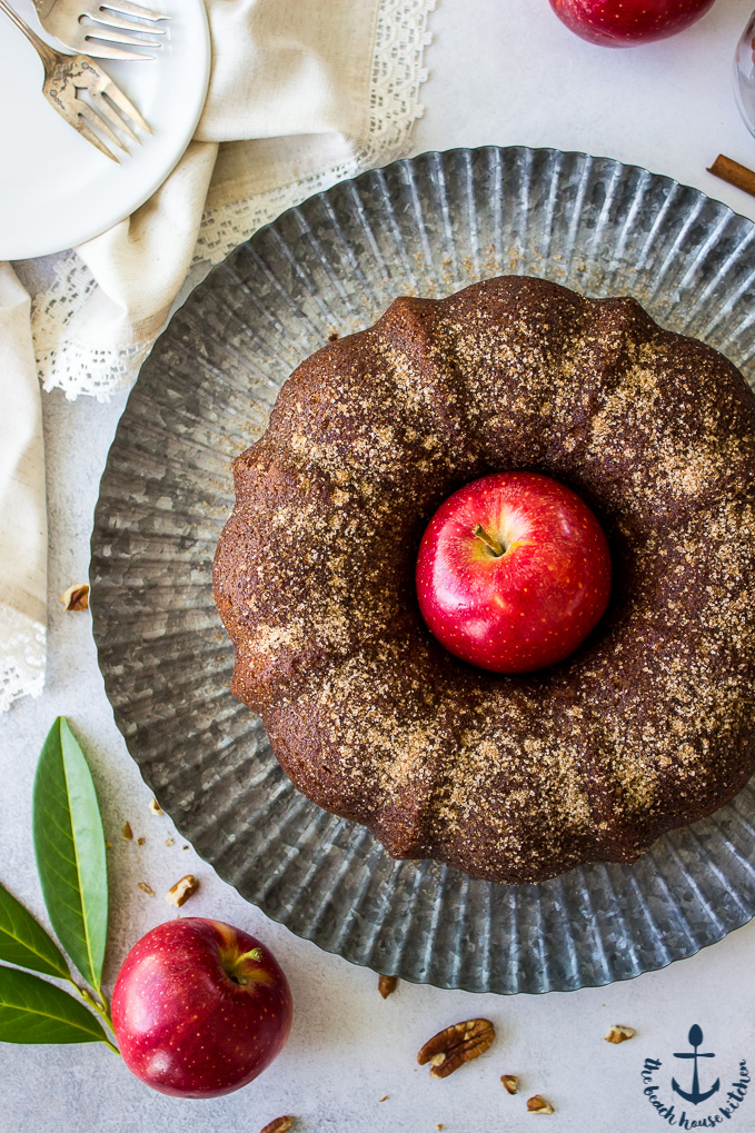 Overhead photo of Apple Cider Doughnut Bundt Cake with Pecan Brown Sugar Ripple with a red apple in the middle of cake on a silver tray.
