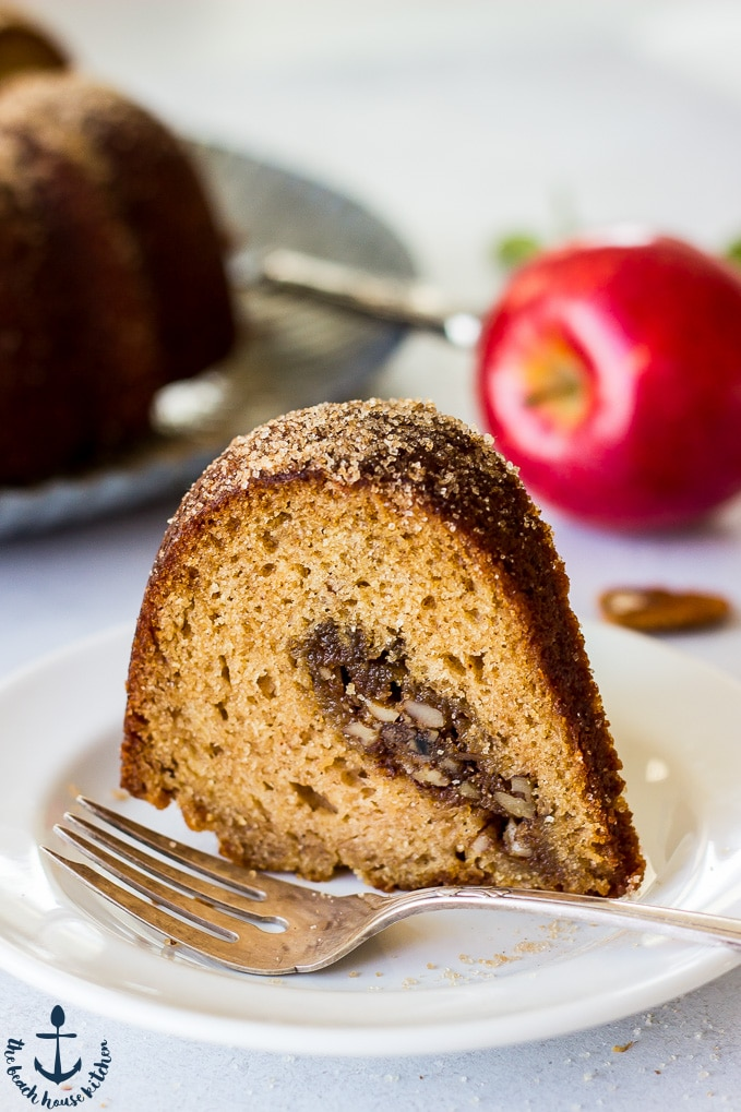 Slice of Apple Cider Doughnut Bundt Cake with Pecan Brown Sugar Ripple on a white plate with a silver fork and an apple in the background.