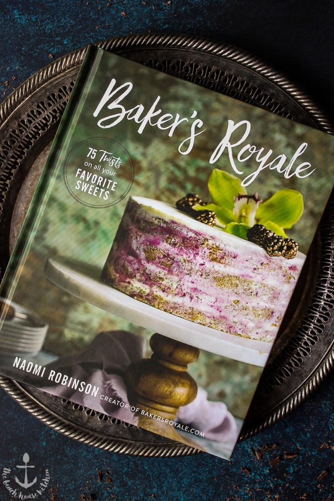Baker's Royale cookbook with a cake on a pedestal tray featured on cover on a silver tray.