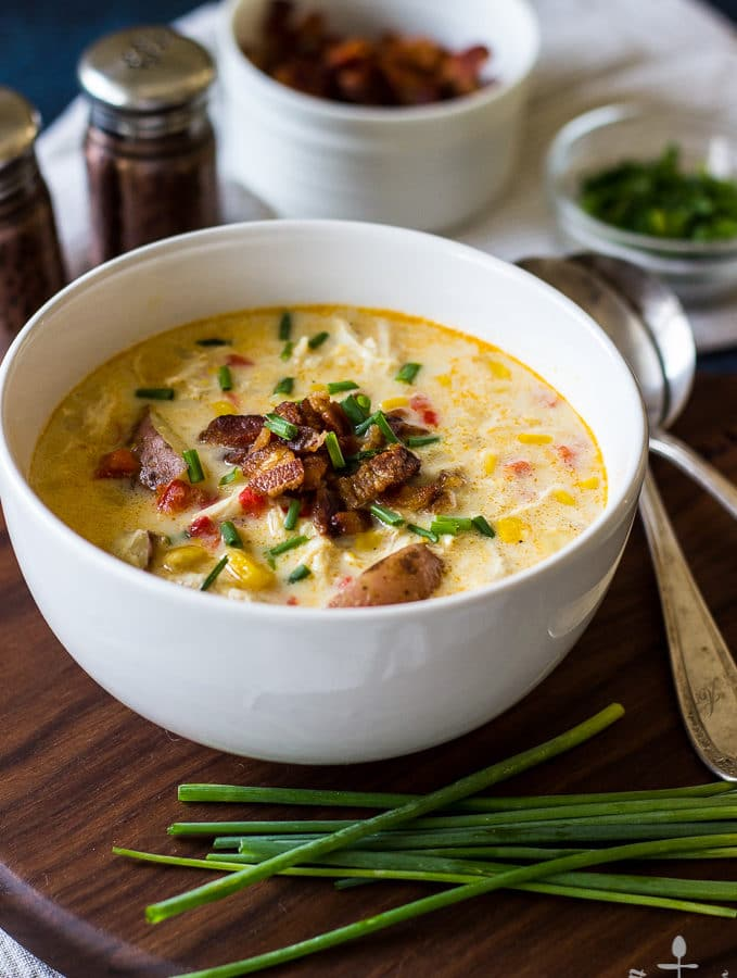 Creamy Chicken Corn Chowder with Bacon in a white bowl with bacon and chives on top, on a dark wood tray with chives in front of bowl.