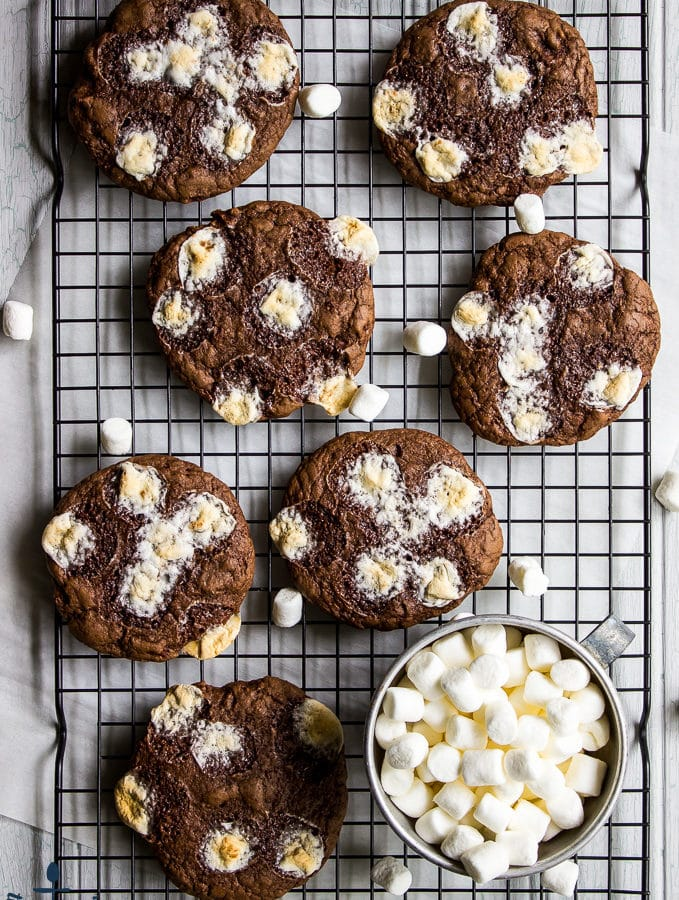 Hot Chocolate Marshmallow Cookies on baking rack with a silver cup filled with mini marshmallows.