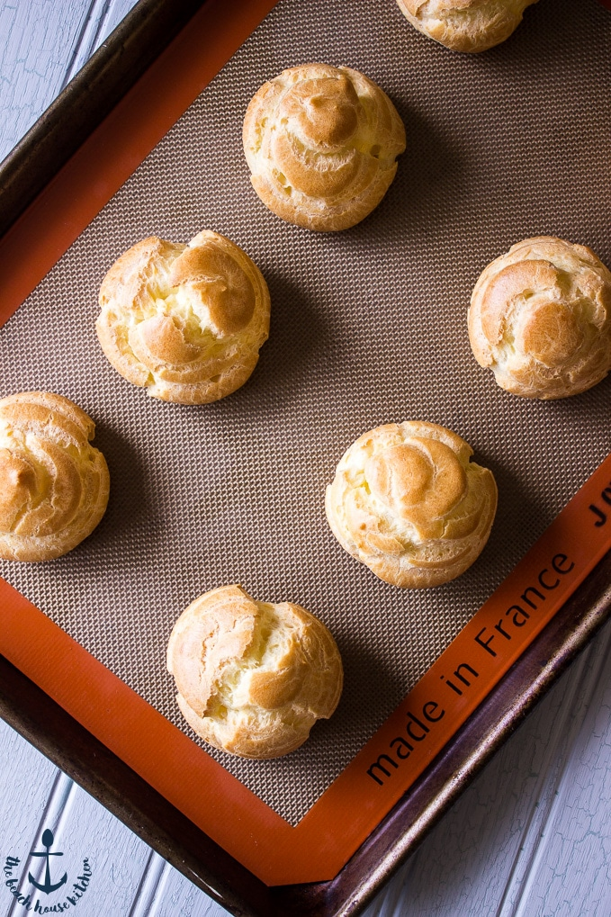 Baked cream puffs on silpat lined baking sheet.