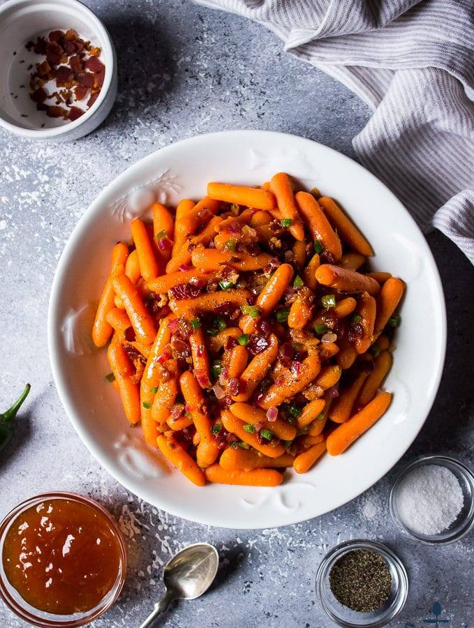 Apricot Glazed Carrots with Bacon and Jalapenos in a white bowl surrounded by bowl of glaze, bowl of bacon, salt and pepper.