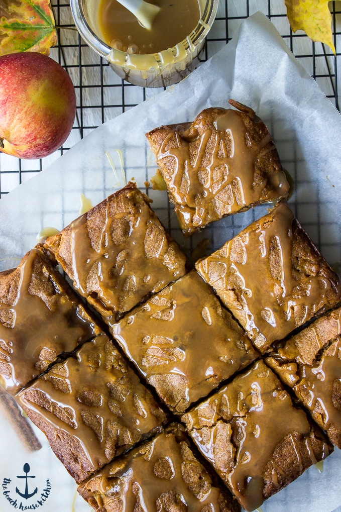 Overhead photo of Caramel Glazed Apple Butter Blondies on a sheet of white parchment paper over a wire cooling rack.