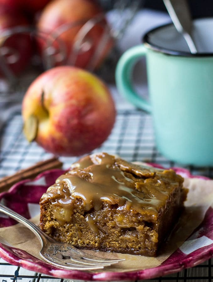 Caramel Glazed Apple Butter Blondie on a red and white check plate with an apple and green mug in background.