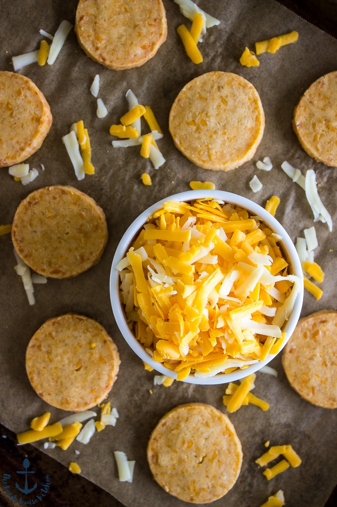 Overhead photo of Cheddar Cheese Coins on a baking sheet lined with parchment paper and a white bowl filled with shredded cheddar cheeses.