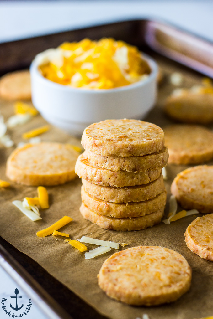Stack of Cheddar Cheese Coins on baking sheet lined with parchment with white bowl filled with shredded cheddar cheese.