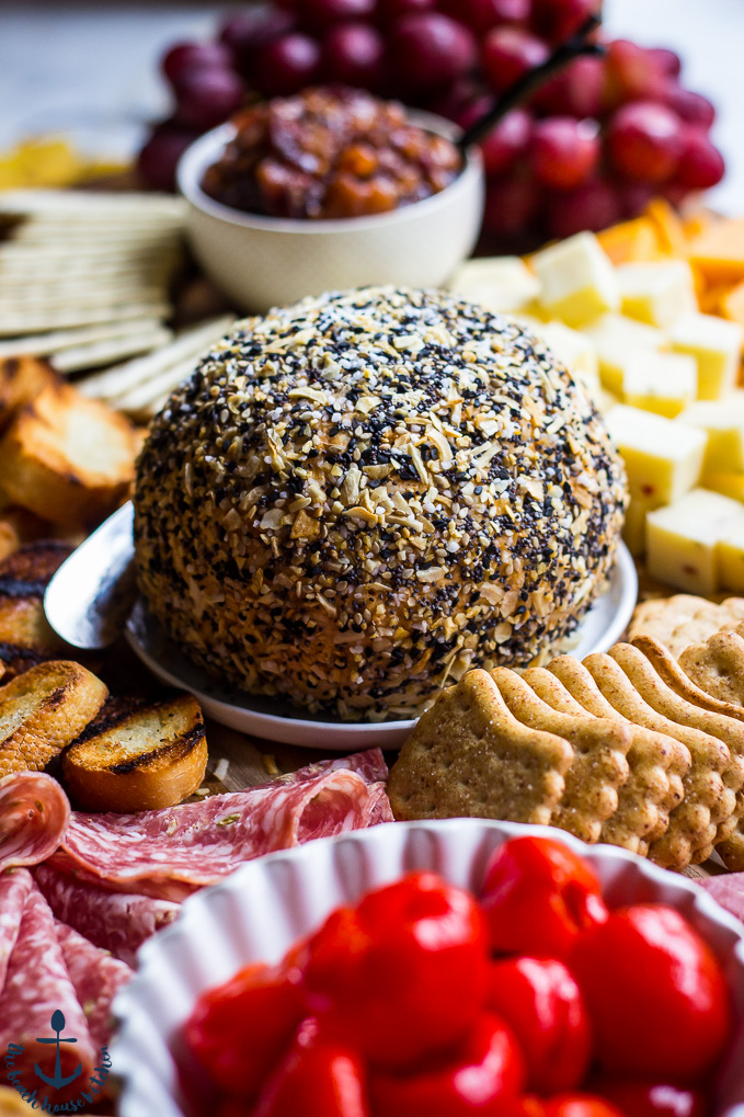 Everything Cheddar Horseradish Cheese Ball surrounded by crackers, salami, peppers and grapes.