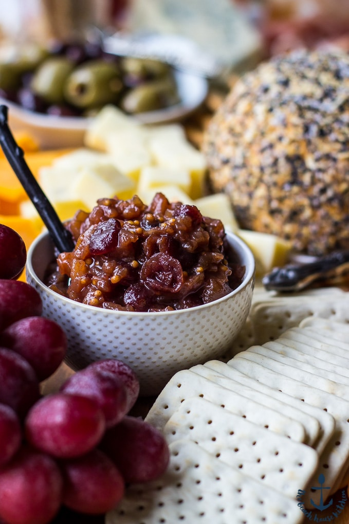 Pear Cranberry Bourbon Chutney in a white bowl surrounded by crackers, grapes, olives and cheeses.