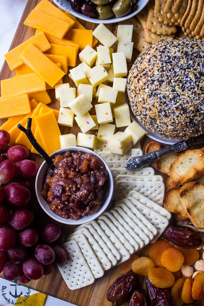 Overhead photo of pear cranberry bourbon chutney in a small bowl surrounded by crackers, cheeses, cheese ball, grapes and fruits.