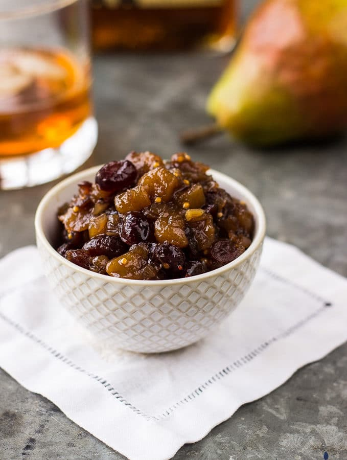 Pear Cranberry Bourbon Chutney in a small white bowl, on a white napkin with a pear and glass of bourbon in background.