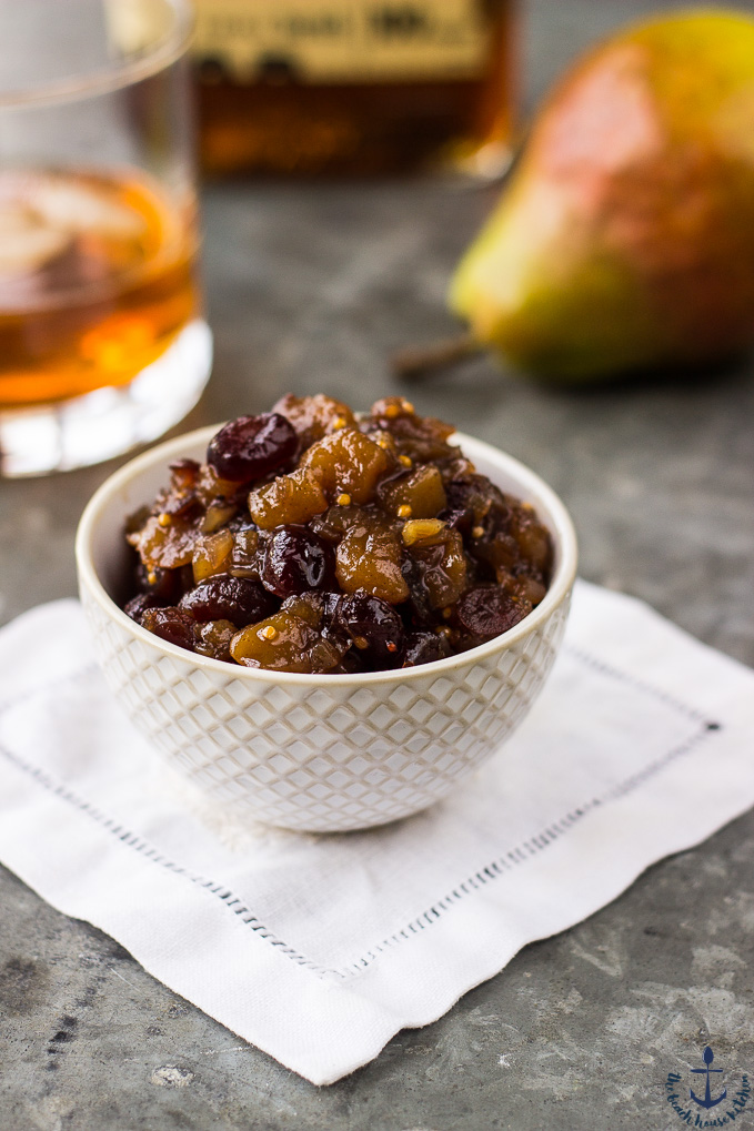 Pear Cranberry Bourbon Chutney in a small white bowl on a white napkin with a pear and glass of bourbon in background.
