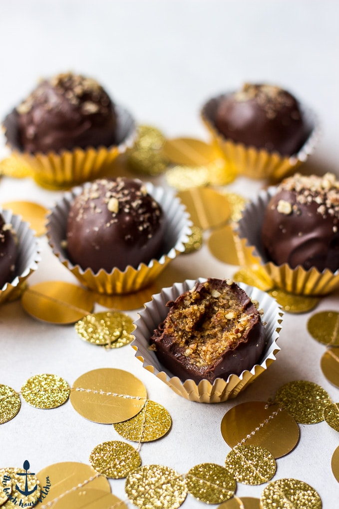 Pecan Pie Truffles, one with a bite taken out, in gold foil cups with gold confetti.