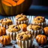 Pumpkin Chocolate Chip Muffins on a silver tray with carved pumpkin in background.