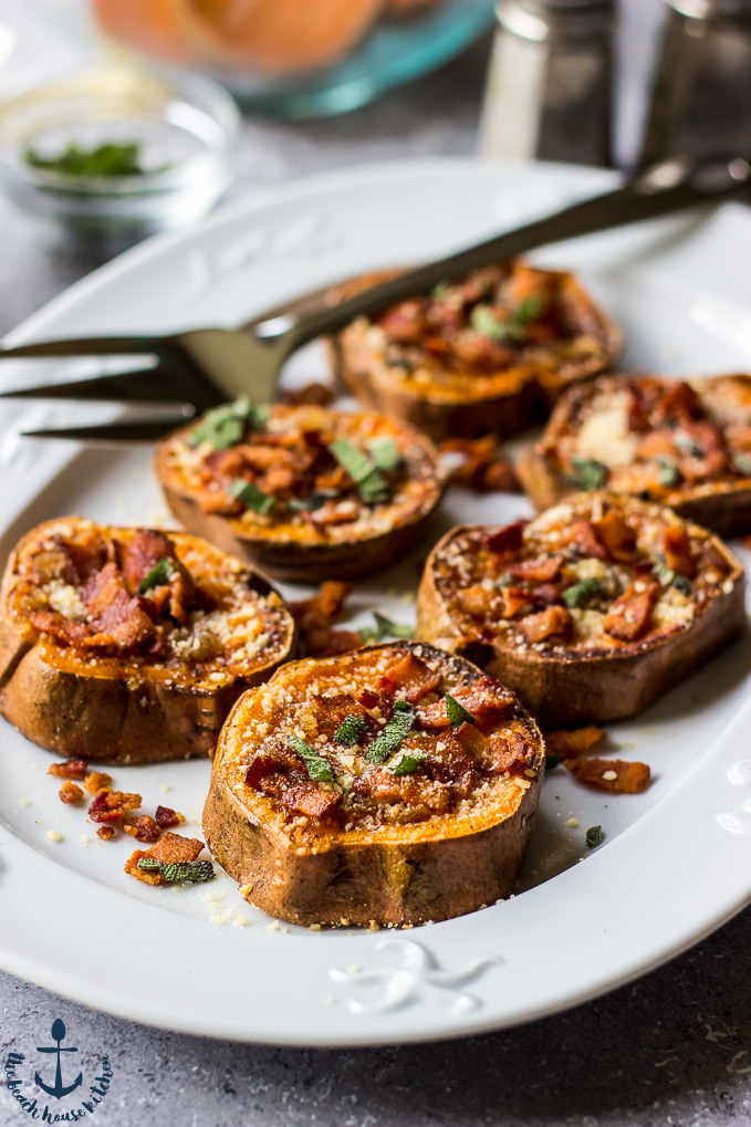 A white oval plate filled with smashed sweet potatoes, browned butter, parmesan, bacon and sage with a serving fork.