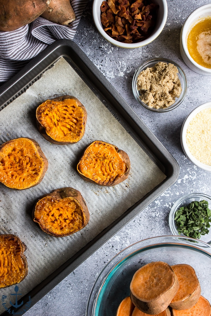 Overhead photo of sweet potato slices on baking sheet, with ingredients in bowls surrounding tray.