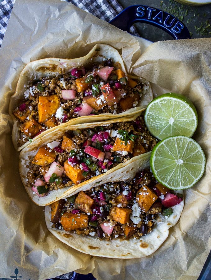 Three chipotle sweet potato quinoa tacos in a blue dish lined with brown parchment paper and a sliced lime.