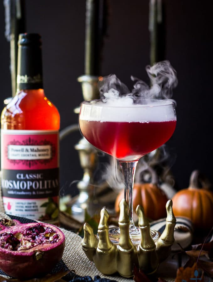 Red Vampire's Venom Cocktail with dry ice smoke bubbling in a gold skeleton hand with candles and cocktail bottle in background.