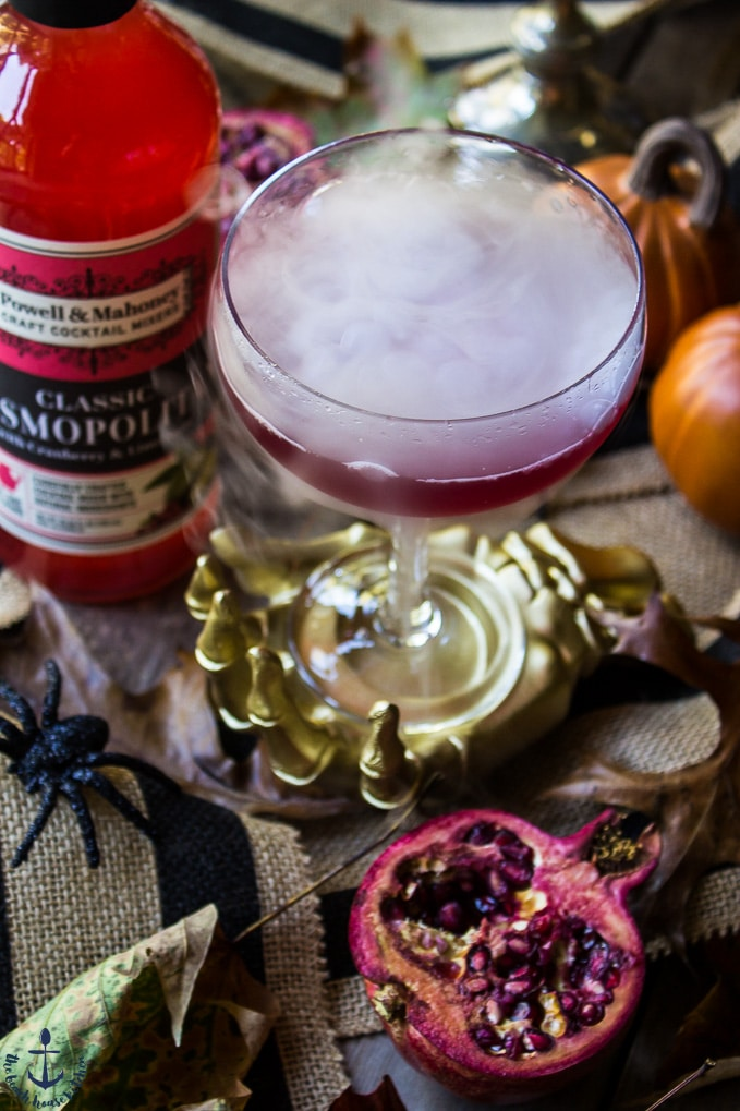The Vampire's Venom Cocktail with dry ice bubbling in a gold skeleton hand with cocktail mixer bottle and half a pomegranate.