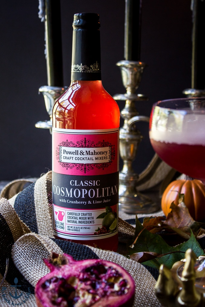 Red bottle of cocktail mixer with pomegranate, striped burlap ribbon and candles in the background.