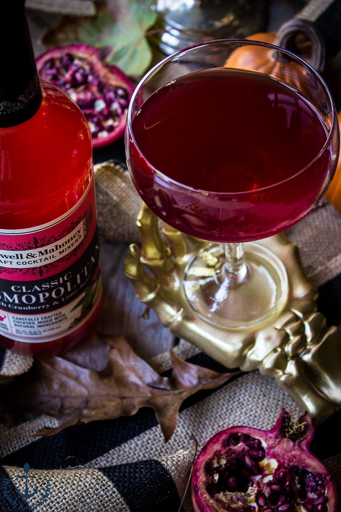 The Vampire's Venom Cocktail in a gold skeleton hand with a red bottle of cocktail mixer and a half a pomegranate.