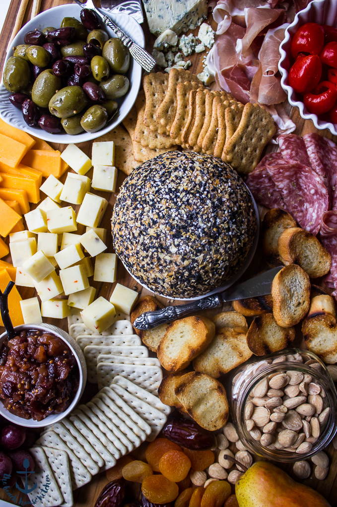 Epic Fall Cheese Board with Everything Cheddar Horseradish Cheese Ball surrounded by meats, fruits, crackers, olives, and peppers.