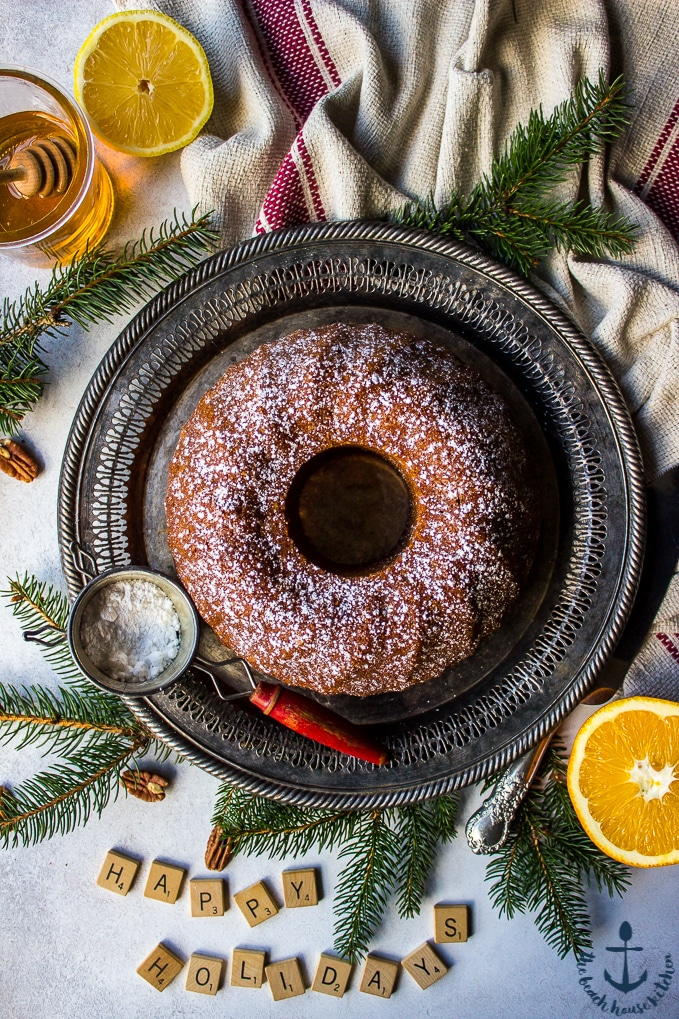 Overhead photo of Honey Pecan Bundt Cake on silver tray with greens, scrabble tiles spelling Happy Holidays, cake knife, sifter, honey and lemon in background.