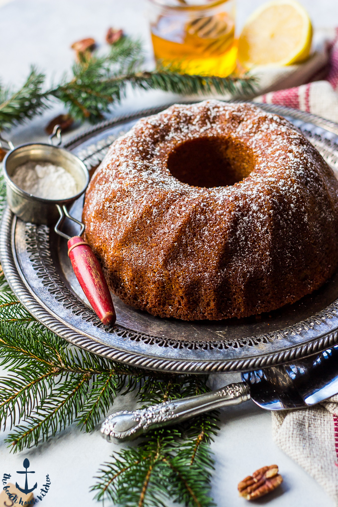 Honey Pecan Bundt Cake on silver tray with greens, cake knife, sifter, honey and lemon in background.