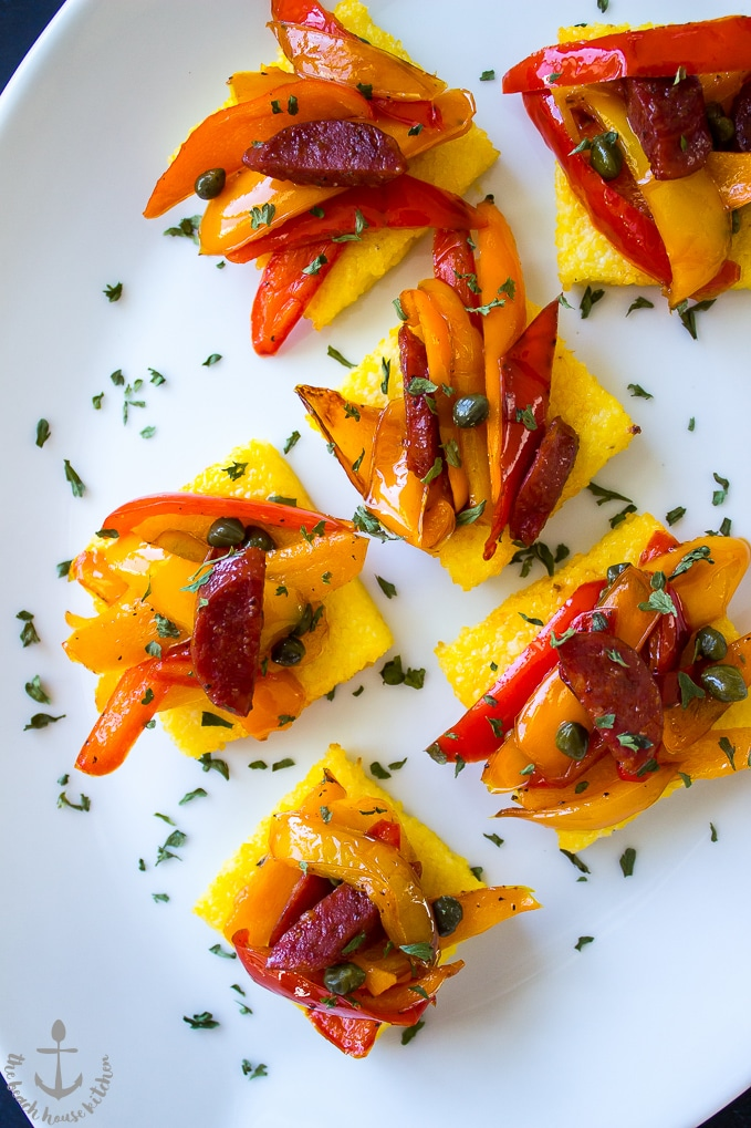 Up close photo of Sweet Pepper and Chorizo Bruschetta Polenta Bites on white platter.