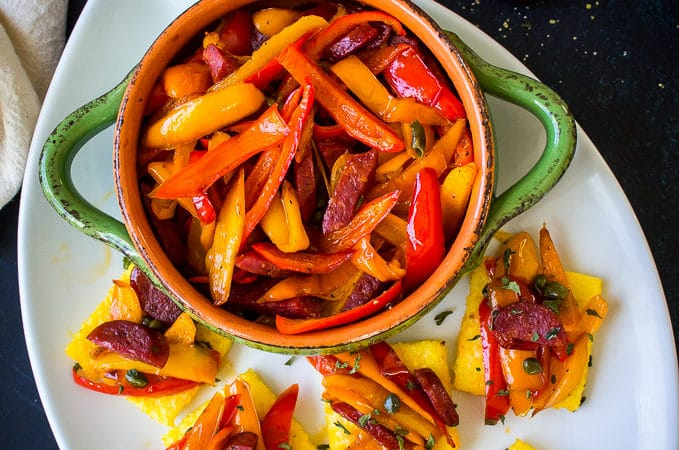 Sweet Pepper and Chorizo Bruschetta Polenta Bites on a white oval platter with a green bowl filled with red and yellow pepper strips
