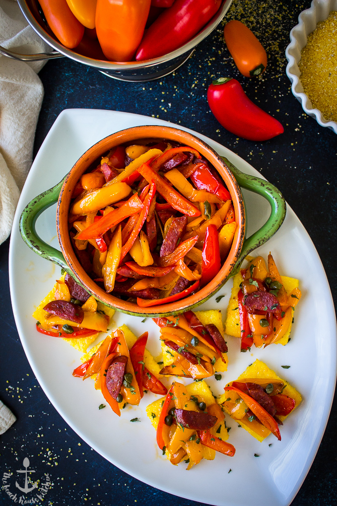 Sweet Pepper and Chorizo Bruschetta Polenta Bites on a white oval platter with a green bowl filled with red and yellow pepper strips.