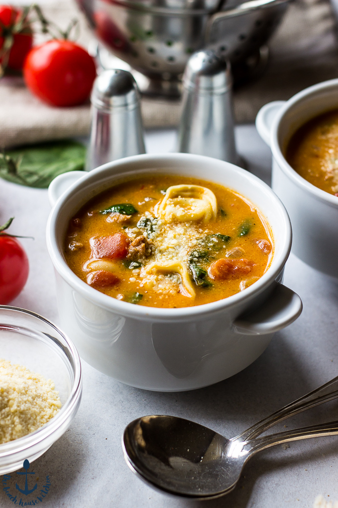 Tomato Tortellini Stew in white bowls with tomatoes on the vine, parmesan cheese in small bowl, salt and pepper shakers, spoons and colander.