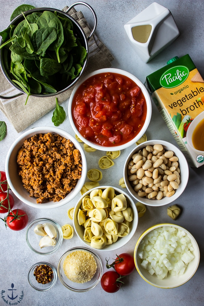 Ingredients for tomato tortellini stew in individual bowls.