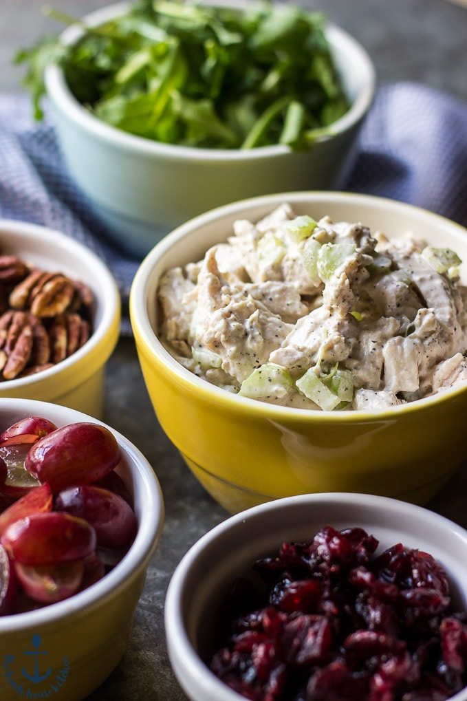 Close up photo of turkey salald in yellow bowl, cranberries, grapes, pecans and arugula in bowls.