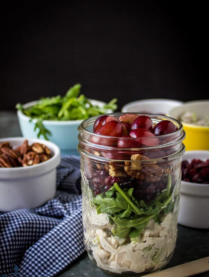 Turkey Salad with Grapes, Pecans and Cranberries in a Jar with pecans and argula in white bowls and blue and white checked napkin.