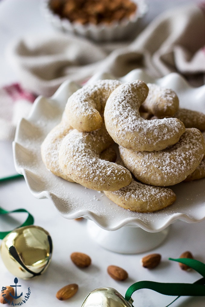 Almond Crescents dusted with confectioners' sugar on white pedestal plate with jingle bells in background.