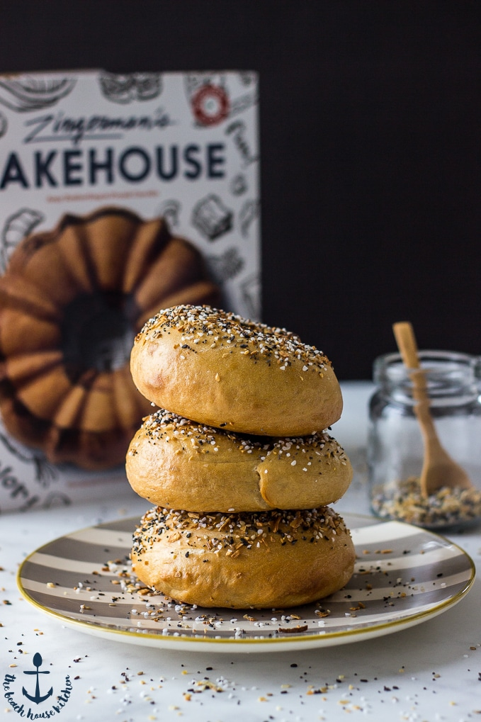Three Everything Bagels stacked on a striped plate with a cookbook and bagel seasoning in a jar in background.