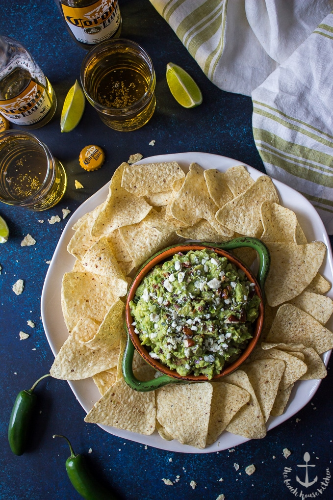 Overhead shot of bacon fig guacamole on a platter with tortilla chips with beer, limes and jalapenos in the background.