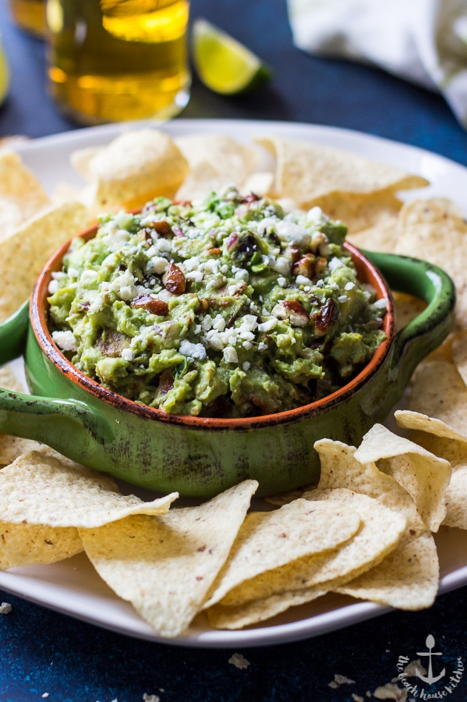 Bacon fig guacamole in a green bowl on a white platter surrounded by tortilla chips.