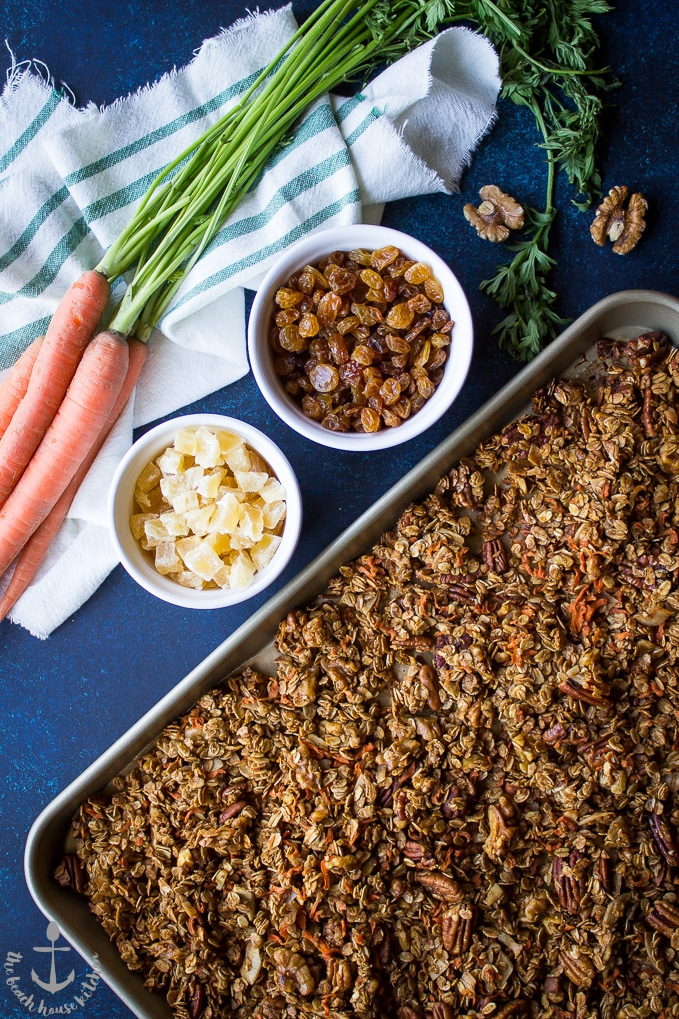 Overhead shot of baked carrot cake granola on baking sheet with dried pineapple and golden raisins in bowls and bunch of carrots on the side.
