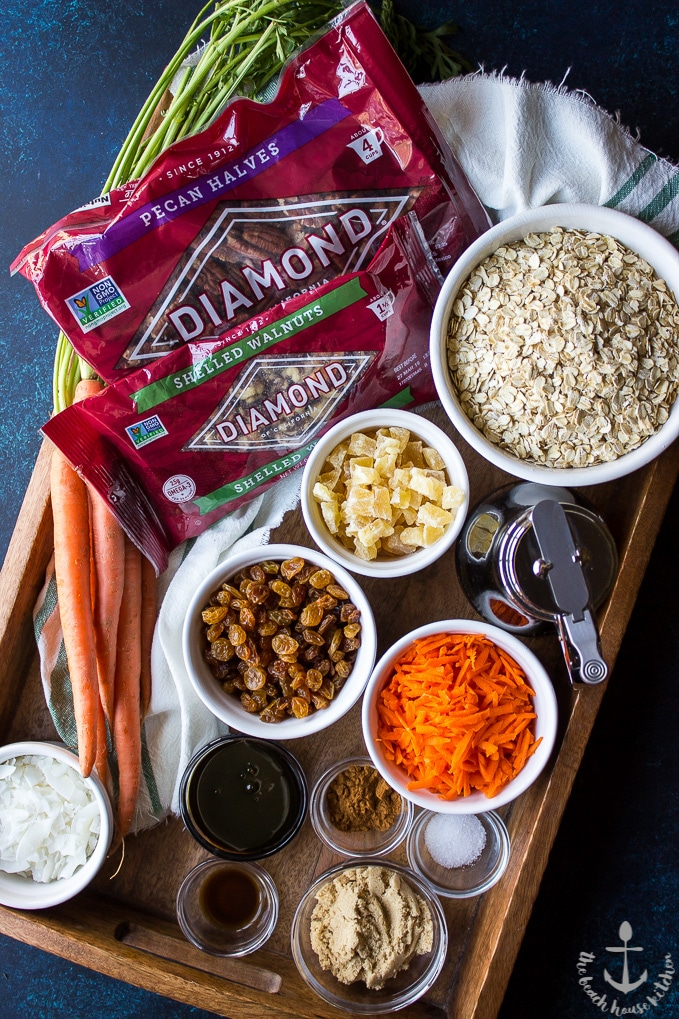 Overhead shot of ingredients for carrot cake granola. Bags of pecans, walnuts, oats, dried pineapple, golden raisins, shredded carrots, coconut, brown sugar in bowls.