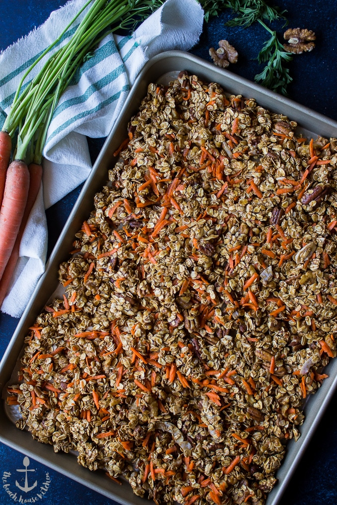 Overhead shot of pre-baked carrot cake granola on baking sheet with bunch of carrots.