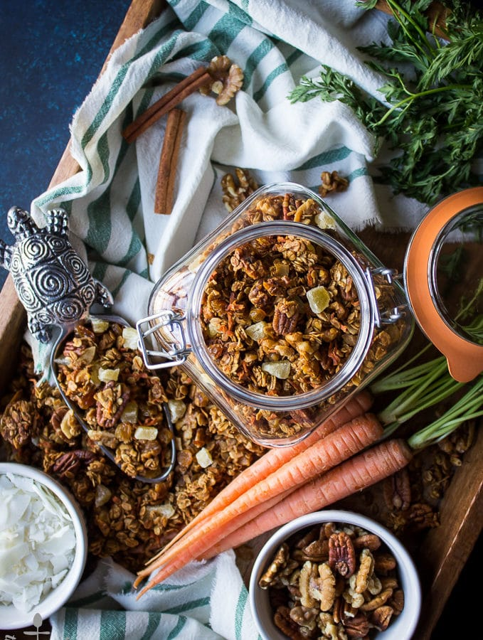 Overhead shot of carrot cake granola in jar on try with bowls of nuts and coconut, carrots, and scooper filled with granola.
