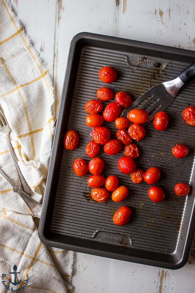 Overhead shot of a baking sheet with roasted grape tomatoes on a white wood background.