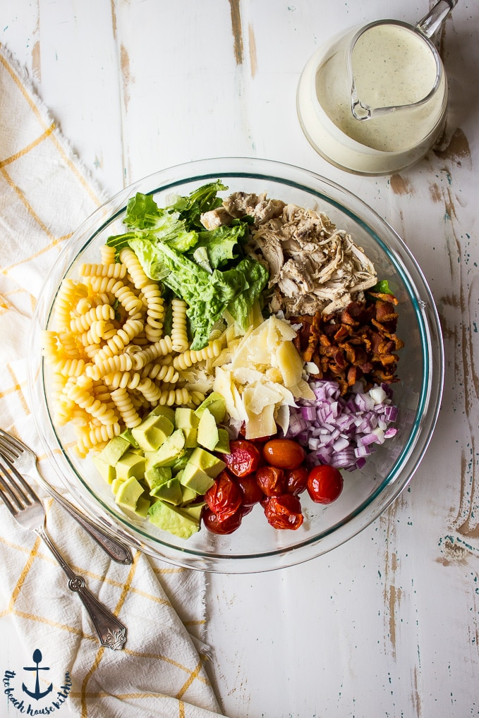 An overhead shot of a glass bowl filled with chicken bacon avocado caesar pasta salad ingredients on a white background.