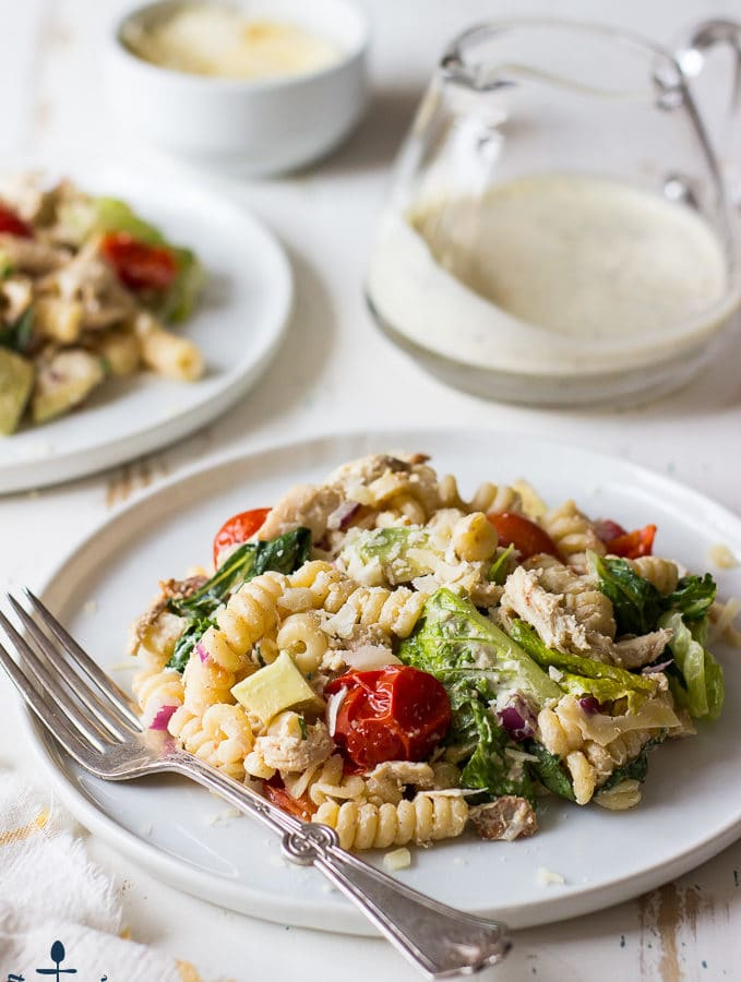 A round, white plate topped with a pasta salad filled with tomatoes, greens and spiral noodles with a silver fork on a white wood surface.