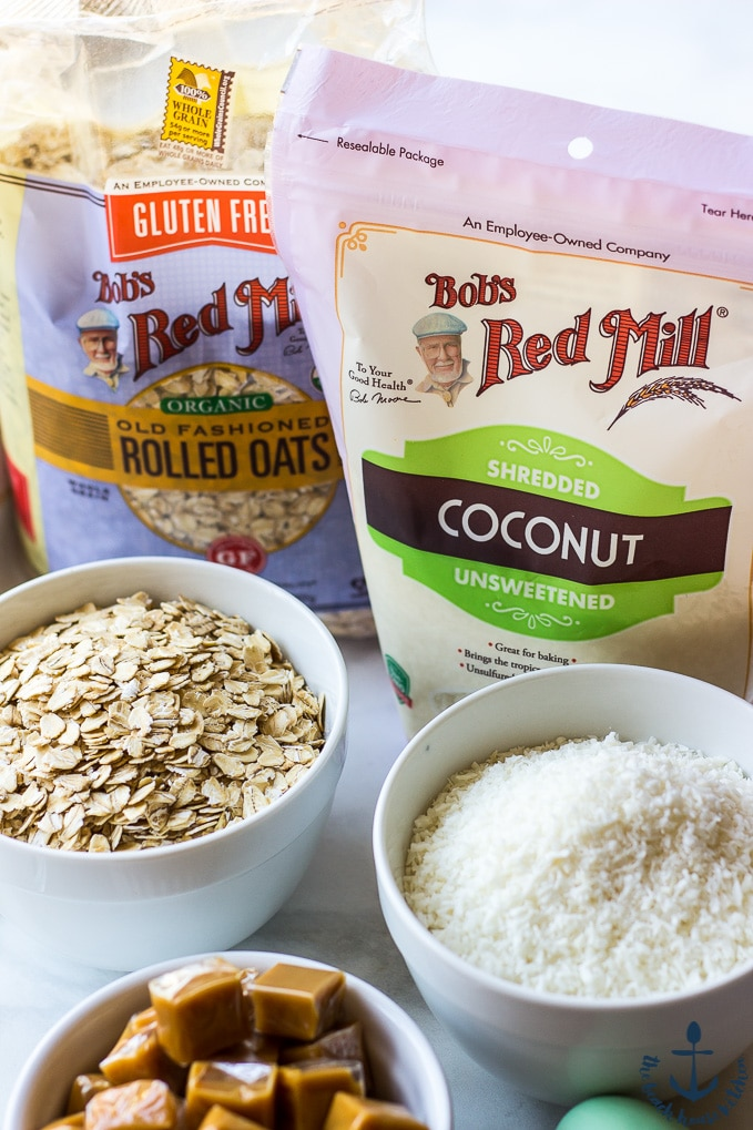 A bag of Bob's Red Mill's Coconut and Rolled Oats with coconut, oats and caramels in separate bowls.