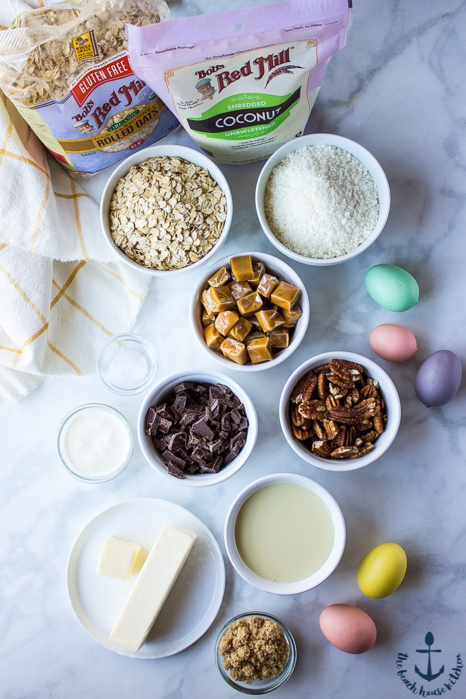 Ingredients for Gluten-Free Coconut Dream Bars in individual bowls on a marble background.